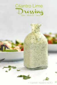 A square glass bottle filled with Cilantro Lime Dressing with two bowls of salad in the background