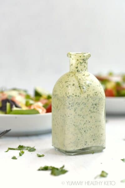 A square bottle filled with Cilantro Lime Dressing sitting in front of two white bowls of salad, surrounded by cilantro leaves