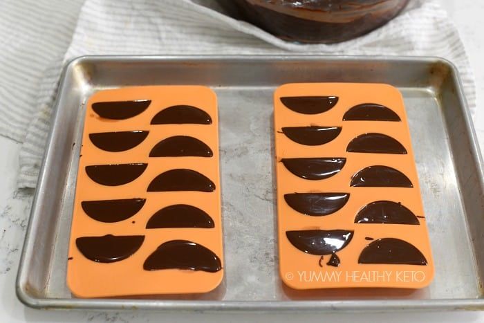 Two orange, silicone trays filled with melted chocolate are sitting on a quarter sheet pan with a glass bowl of chocolate and a gray and white dish towel in the background