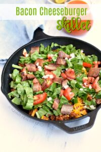 A cast iron skillet with Bacon Cheeseburger Skillet topped with lettuce and tomato. A clear glass pitcher of dressing is in the background