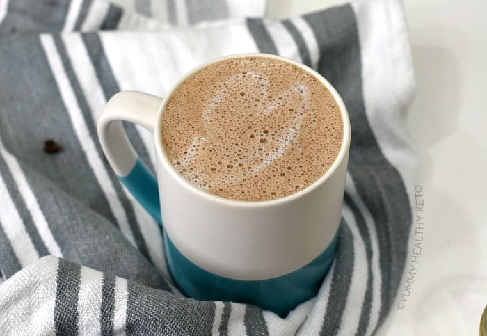 A Keto Mocha with foamy milk on top in a white and blue mug sitting on a white and gray striped towel.