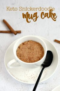 A white coffee mug sitting on a white plate with a black spoon resting on the plate is filled with a Keto Snickerdoodle Mug Cake with cinnamon sticks laying on the white background