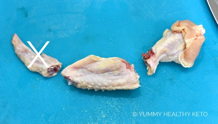 A chicken wing cut into pieces, sitting on a blue cutting mat with a big X through the tip.