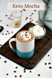 A Keto Mocha in a blue and white mug sitting in front of a small glass bowl of whipped cream, both of which are sitting on a walnut board with a green napkin on the edge, with coffee beans scattered around the white backdrop