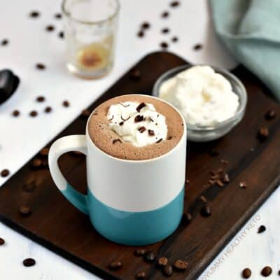 A Keto Mocha in a blue and white mug sitting on a walnut board with a small glass bowl of whipped cream behind it, a green napkin laying on the edge of the board and espresso beans scattered on a white background