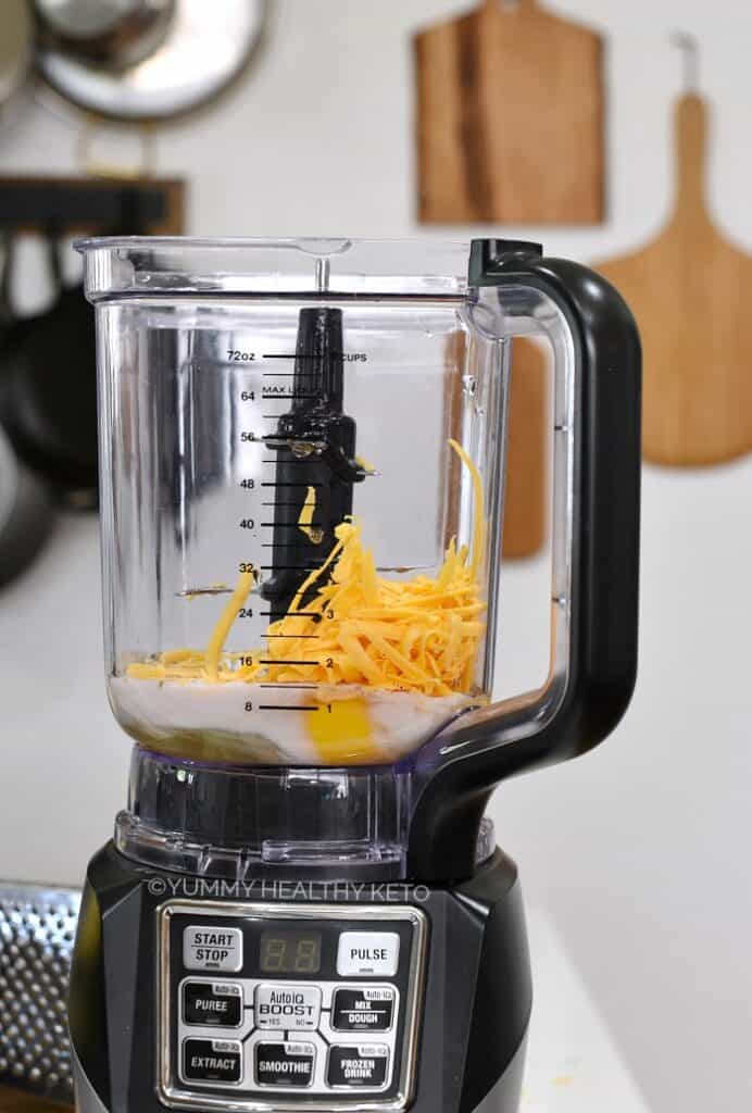 A side view of a blender sitting on the counter with eggs, milk and grated cheese inside.