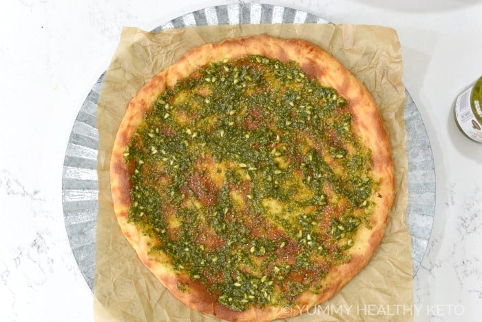 Basil pesto spread on a Fathead pizza crust sitting on a brown parchment paper lined silver charger .