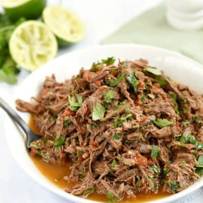 Instant Pot Mexican Shredded Beef in a white bowl with limes and a pale green napkin in the background
