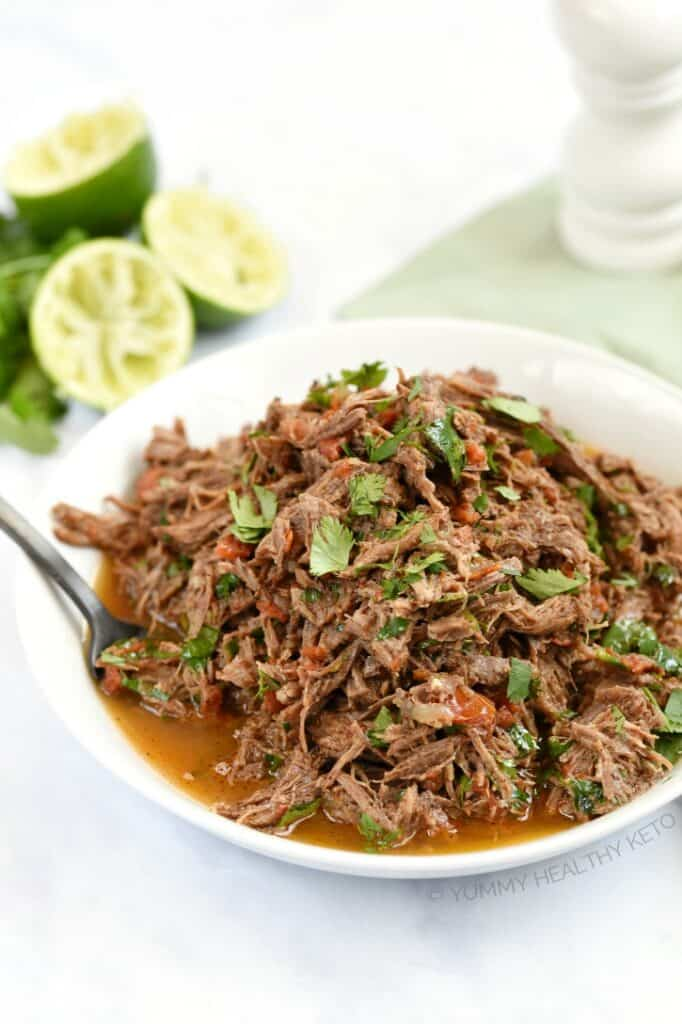 Tender, Instant Pot Mexican Shredded Beef in a white bowl with limes and a pale green napkin in the background.