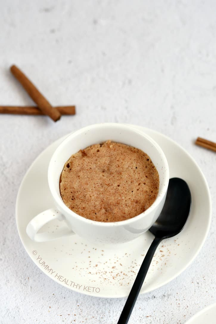A white coffee mug sitting on a white plate filled with a Keto Snickerdoodle Mug Cake with a black spoon resting on the plate and cinnamon sticks laying on a white background