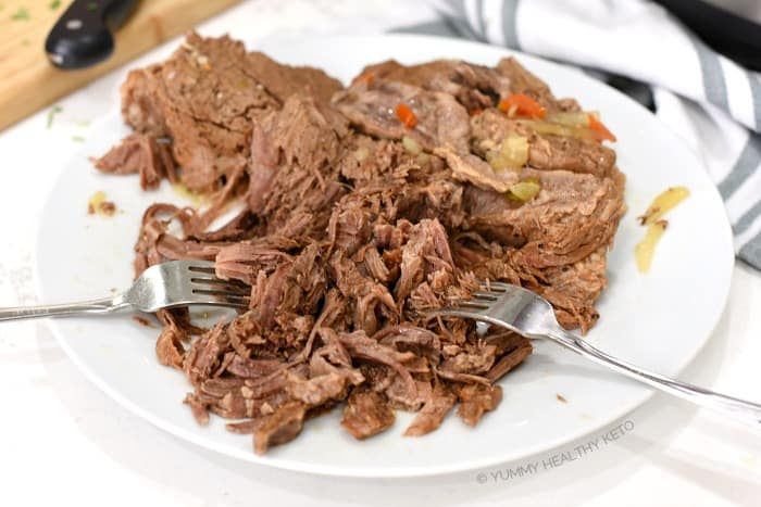 Place cooked roast on a large plate and shred with two forks.