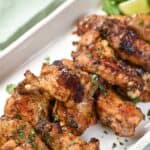 Chili Lime Chicken Wings piled on a white, rectangle platter with cilantro and lime wedges in the corner, sitting on a pale green napkin