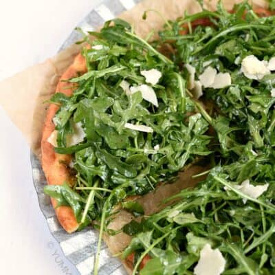 Keto Pesto Pizza with Fresh Arugula on a brown parchment paper lined metal charger sitting on a white counter
