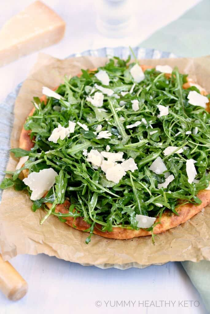 This Keto Pesto Pizza with Fresh Arugula uses Fathead Pizza dough, basil pesto and lots of fresh leafy greens and topped with Parmesan!