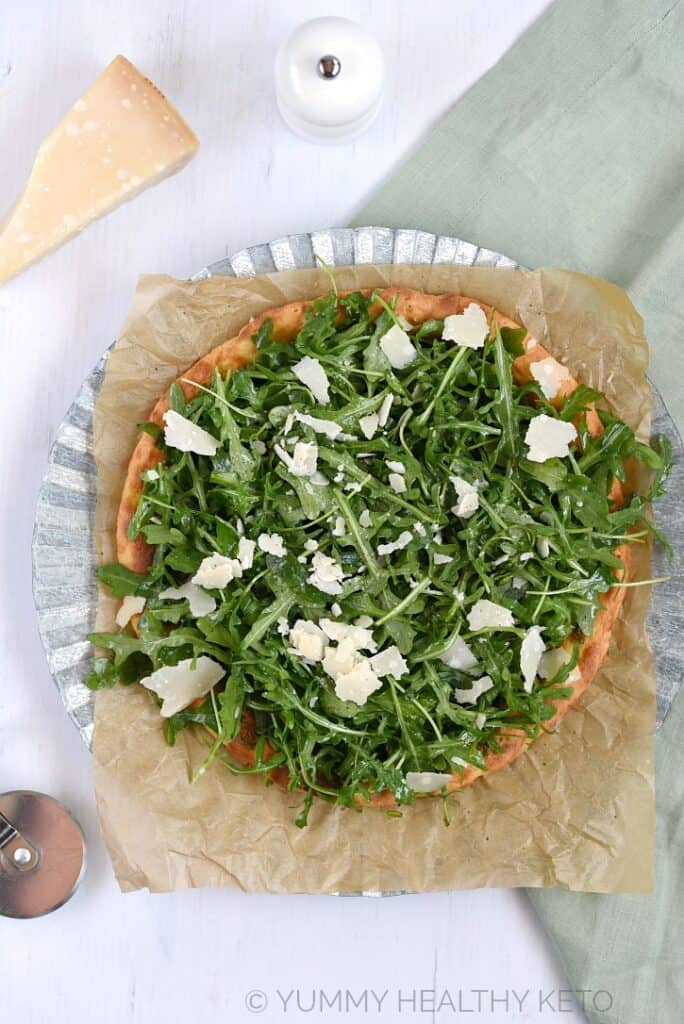 A Keto Pesto Pizza with Fresh Arugula on brown parchment paper sitting on a metal charger and pale green napkin with a wedge Parmesan and a pepper shaker in the background.