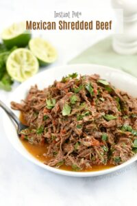 A white bowl filled with Instant Pot Mexican Shredded Beef with limes and a green napkin in the background
