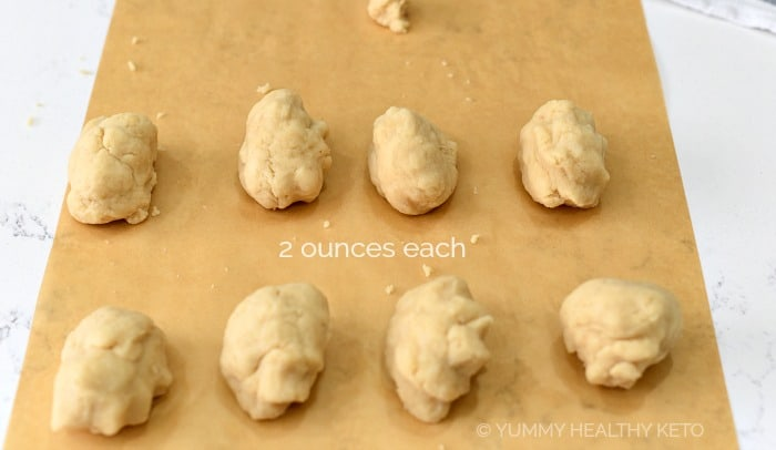 8 balls of dough sitting on a piece of parchment paper.