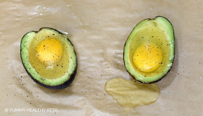 Avocado halves filled with a raw egg and sprinkled with salt and pepper.