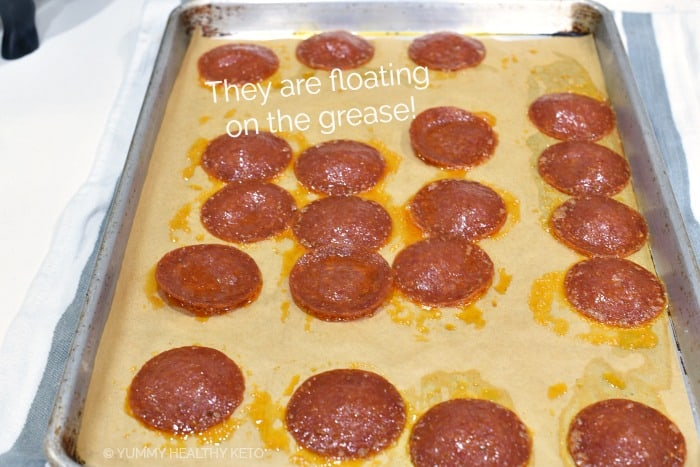 Baked pepperoni chips on a parchment lined baking sheet.