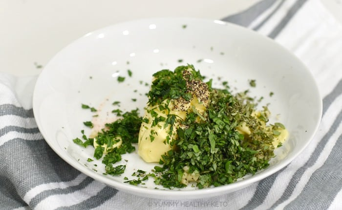 Butter, garlic, salt, pepper and fresh herbs in a white bowl sitting on a gray and white striped towel.