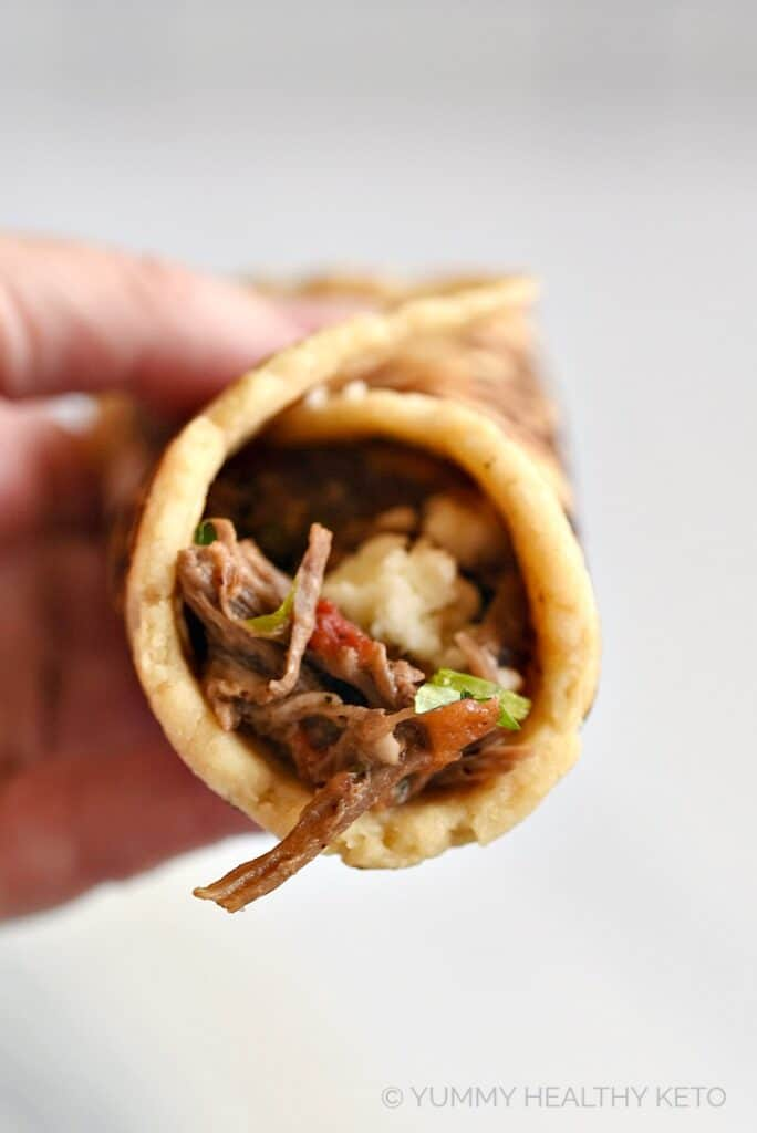 A hand holding a keto almond flour tortilla wrapped around shredded beef and crumbled cheese.