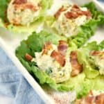 Egg Salad on Lettuce leaves topped with bacon and sitting on a white serving tray