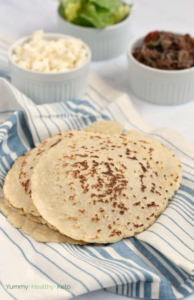 A stack of keto almond flour tortillas on a blue and white striped towel with crumbled cheese, shredded beef and chopped lettuce in bowl in the background