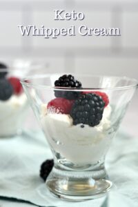 Two glass dessert cups filled with Keto Whipped Cream and topped with fresh raspberries and black berries