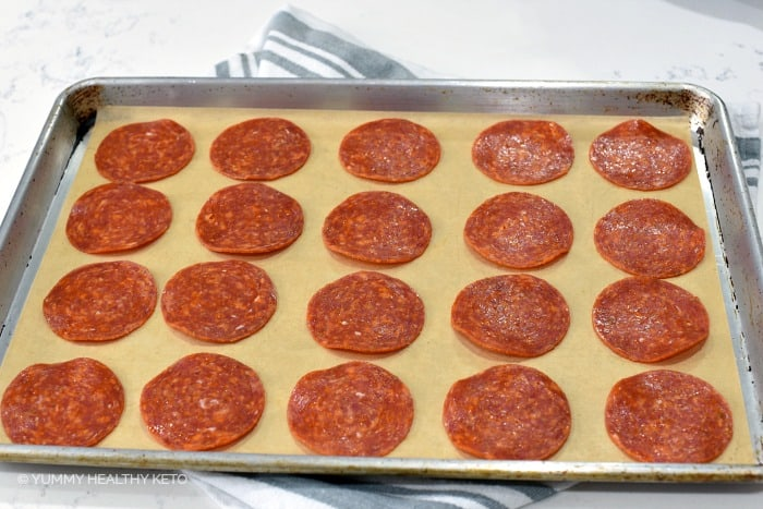 Pepperoni slices laid out on a parchment paper lined baking sheet.