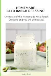 A jar of homemade Keto Ranch Dressing sitting on a green napkin with two bowls of salad in the background.