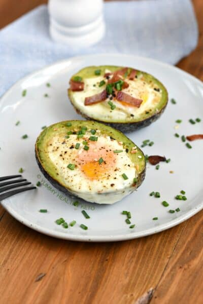 Two Baked Avocado Egg Cups sitting on a plate. One with bacon and chives and the other with everything bagel seasoning