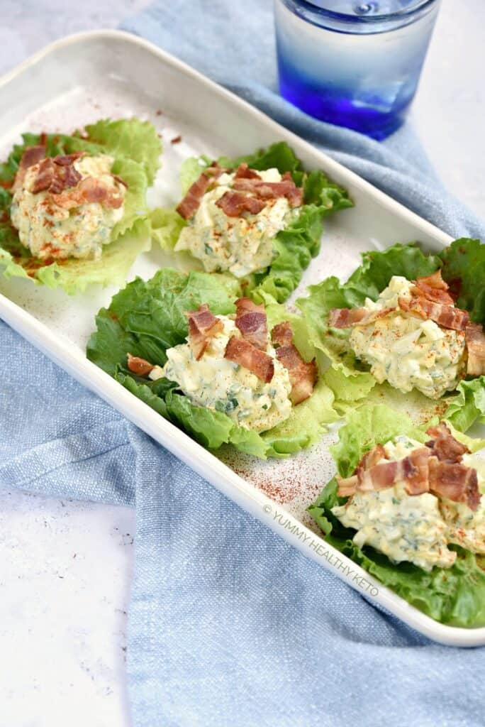 Egg Salad Lettuce Wraps topped with chopped bacon and sprinkled with paprika.