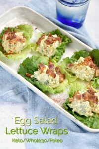 Egg Salad Lettuce Wraps on a white serving tray topped with chopped bacon and paprika