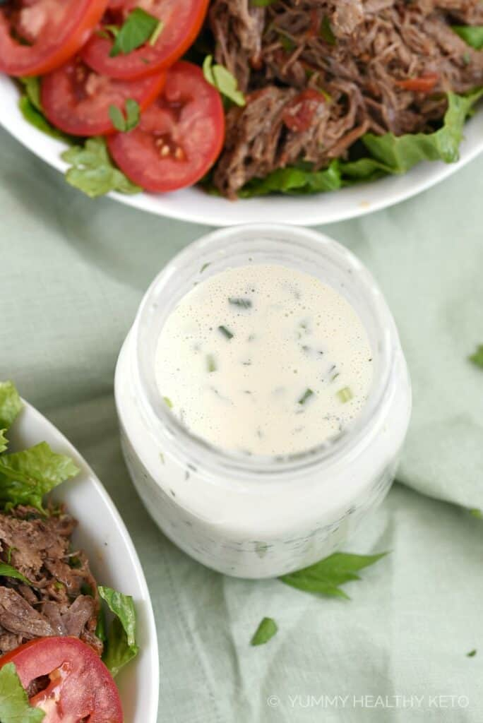Overhead view of Keto Ranch Dressing in a glass mason jar sitting between two bowls of salad.