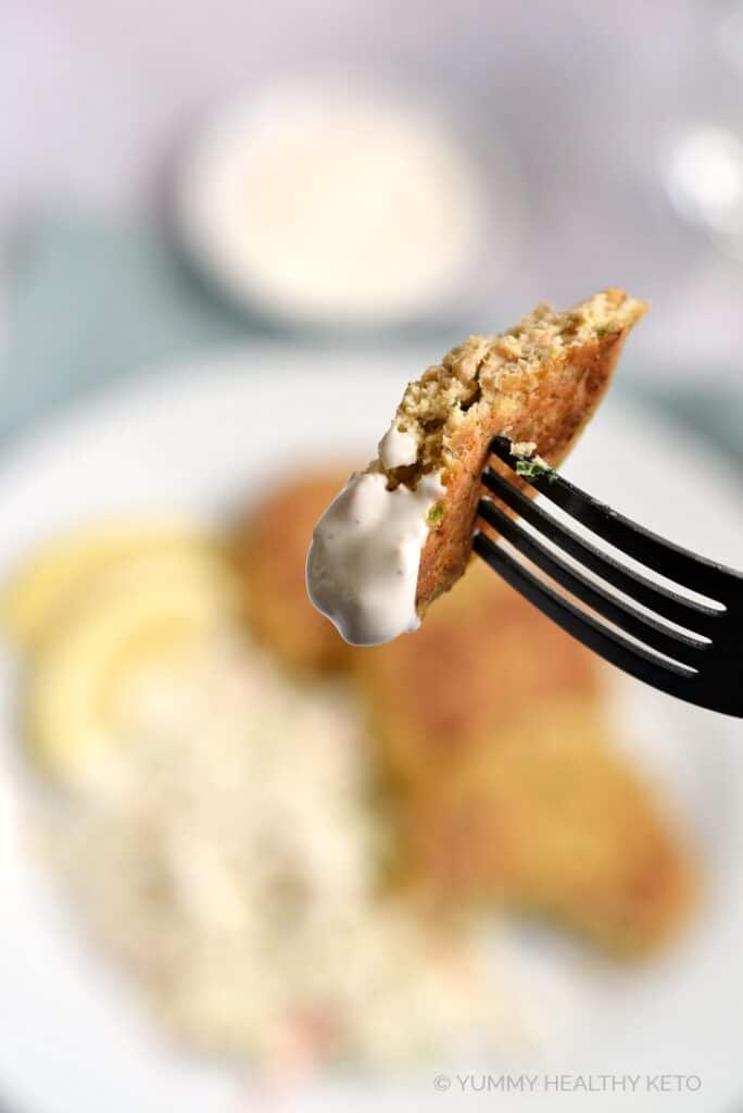 A piece of salmon patty on a fork, dipped in garlic aioli.