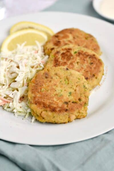 Three Keto Salmon Patties with a side of coleslaw and lemon wedges