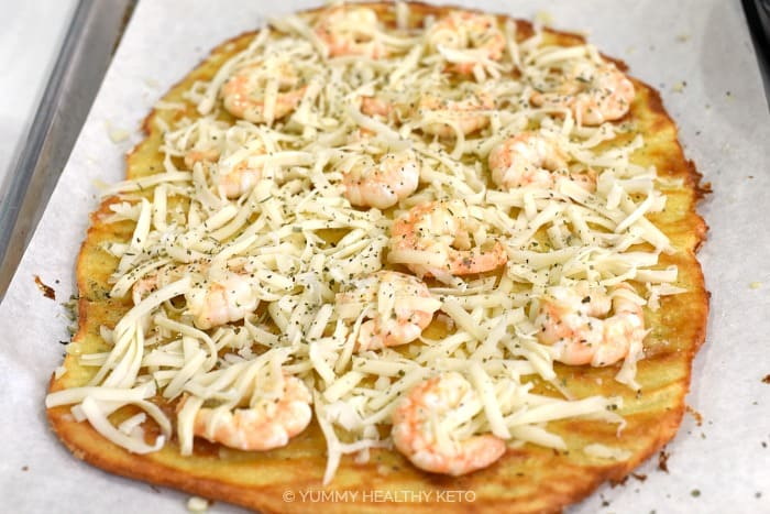 Top the pizza crust with shrimp, shredded cheese and Italian seasoning.
