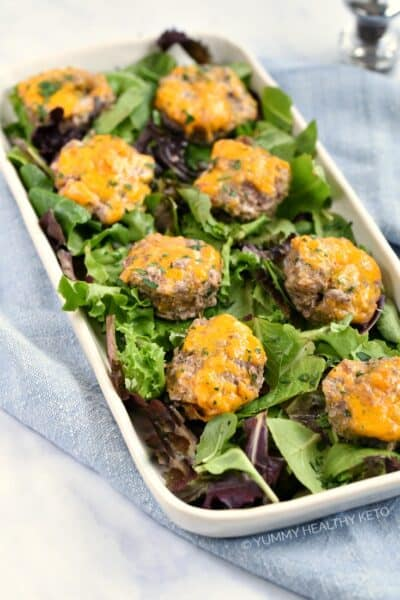 Meatloaf Muffins with cheese and bacon on a rectangle platter covered in lettuce