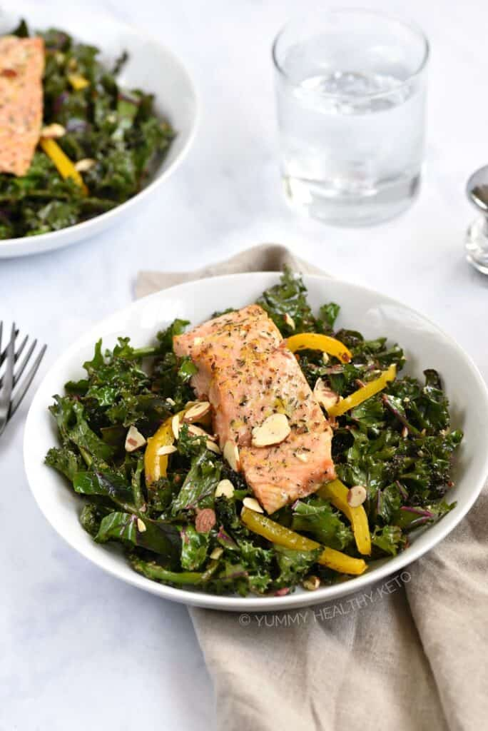 Broiled Salmon resting on a bed of kale, asparagus and bell pepper that has been tossed with a citrus vinaigrette.