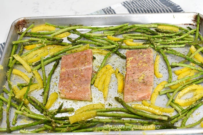 Two salmon fillets added to the asparagus and peppers on the baking sheet.