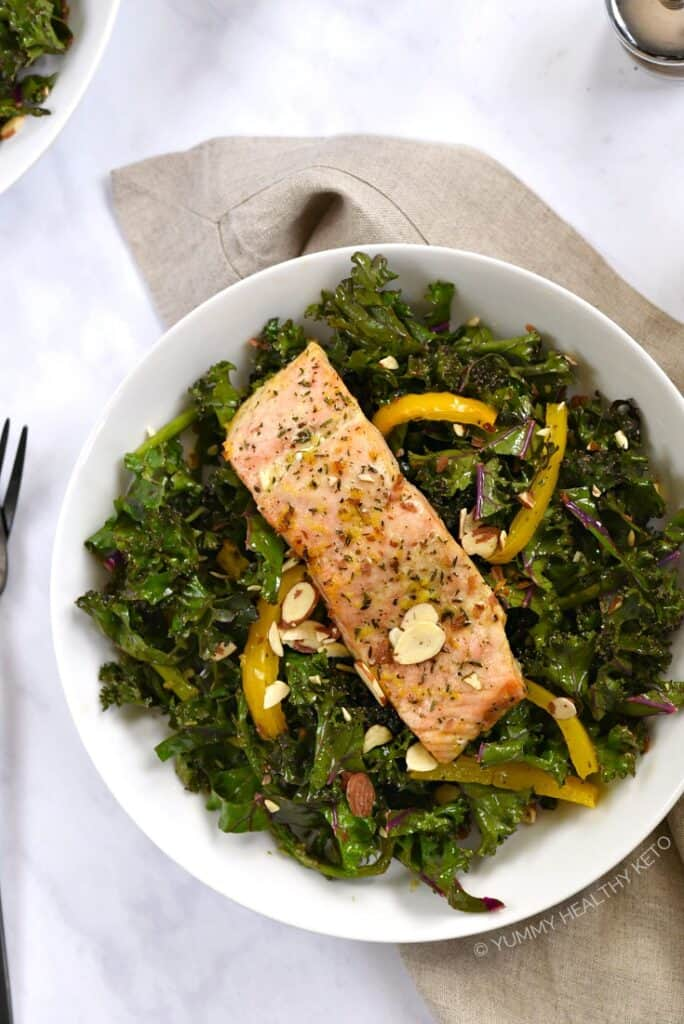 Overhead view of a Broiled Salmon fillet resting on an asparagus and kale salad with bell pepper strips and sliced almonds.