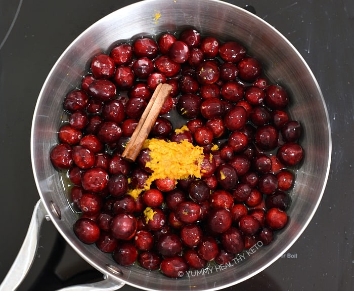 Cranberries, orange zest and juice and a cinnamon stick in a saucepan.