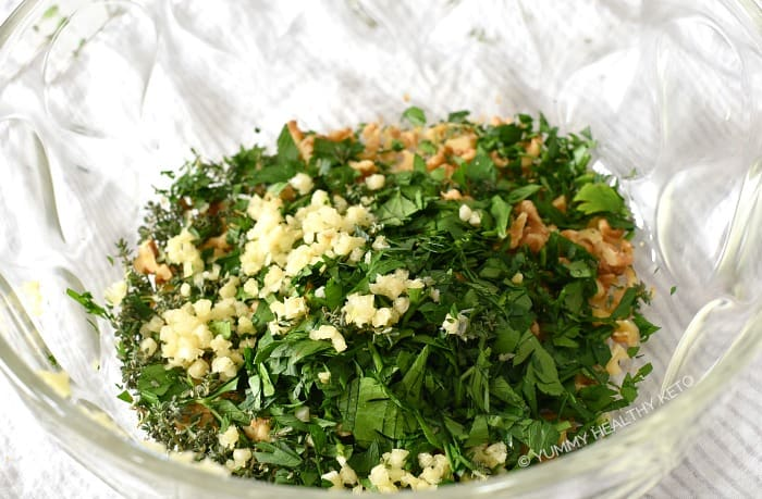 Fresh herbs, garlic and nuts in a large glass bowl.
