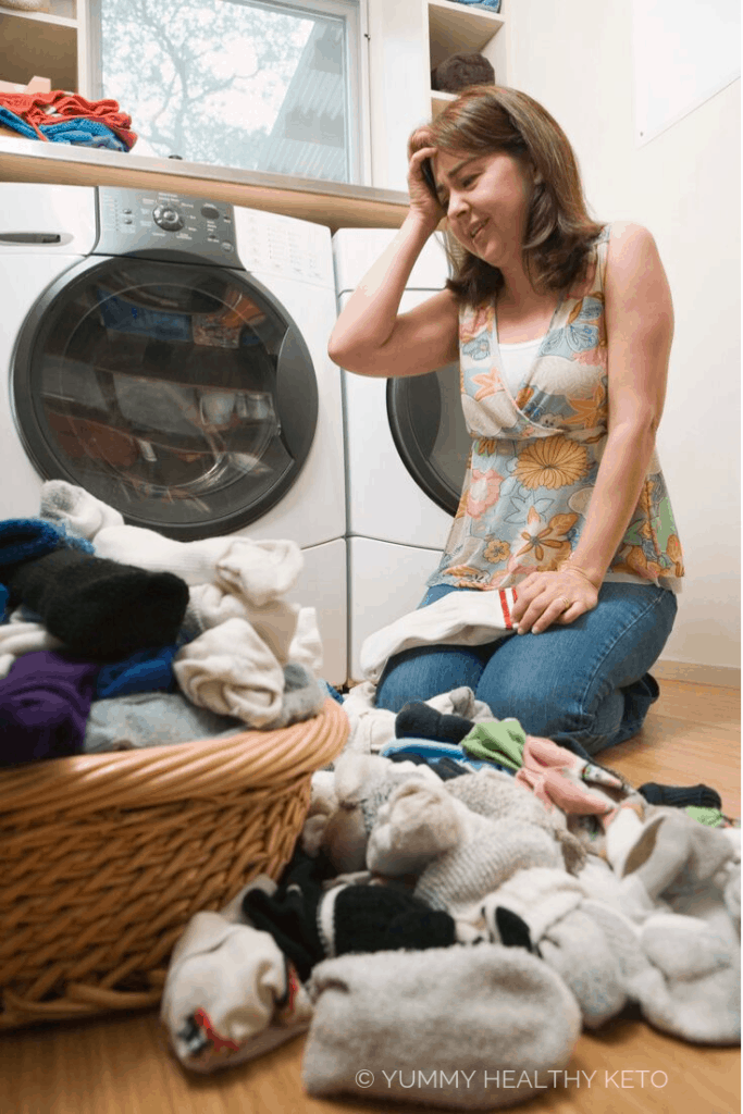 Stressed out woman doing piles of laundry.