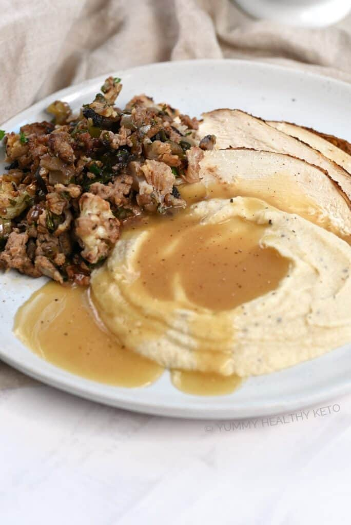 Turkey slices served with Mashed Cauliflower, Keto Gravy and Keto Stuffing.