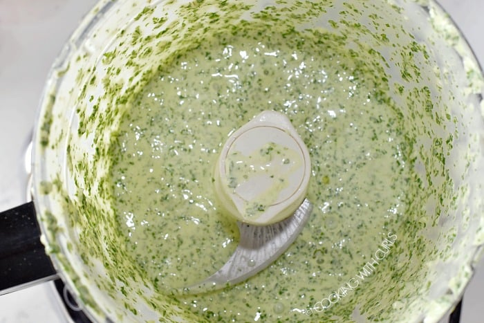Creamy cilantro lime dressing in the bowl of a food processor.