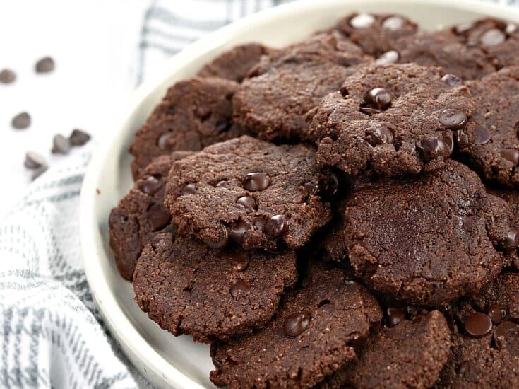 Keto Double Chocolate Chip Cookies piled on a white plate sitting on a gray striped napkin with chocolate chips scattered all around