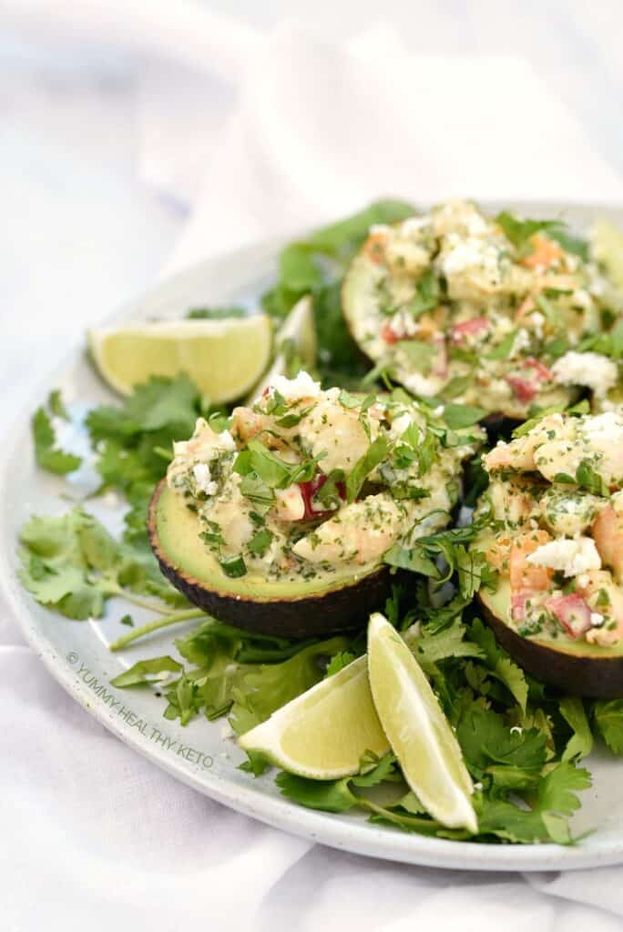 Close up image of Keto Shrimp Stuffed Avocado halves on a bed of cilantro leaves with lime wedges on the side.