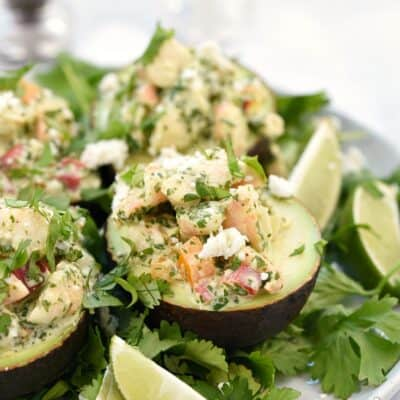 Four Keto Shrimp Stuffed Avocado halves on a cilantro covered plate with lime wedges on the side