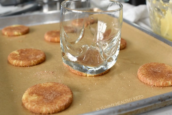 Keto Snickerdoodle Cookies flattened with a glass on a parchment lined baking sheet.